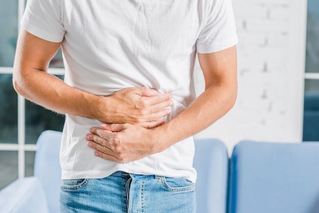 Sección media de un hombre sosteniendo tener dolor en el estómago Foto gratis