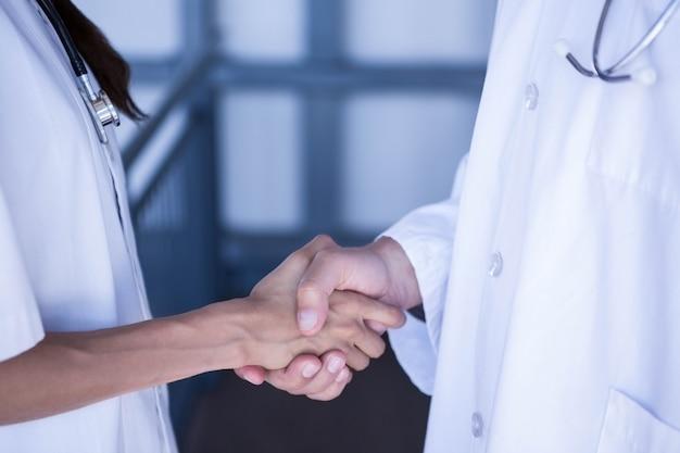 Sección media de médicos dándose la mano en el hospital Foto Premium