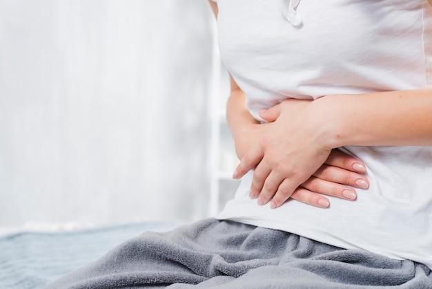Sección media de una mujer con dolor en el abdomen Foto gratis