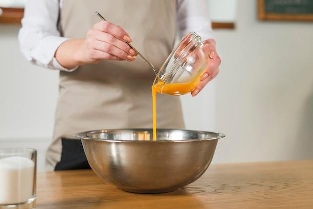 Sección media de la mujer que vierte la yema de huevo en el recipiente de acero inoxidable en la mesa de madera Foto gratis