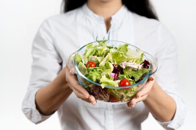 Sección media de mujer sosteniendo un tazón de ensalada vegetariana saludable Foto gratis