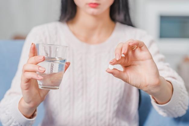 Sección media de una mujer con tableta blanca y vaso de agua en las manos Foto gratis