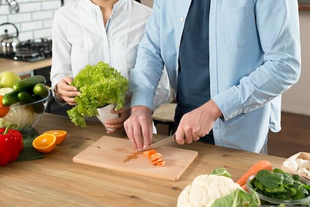 Sección media de pareja preparando la comida en el mostrador de la cocina Foto gratis