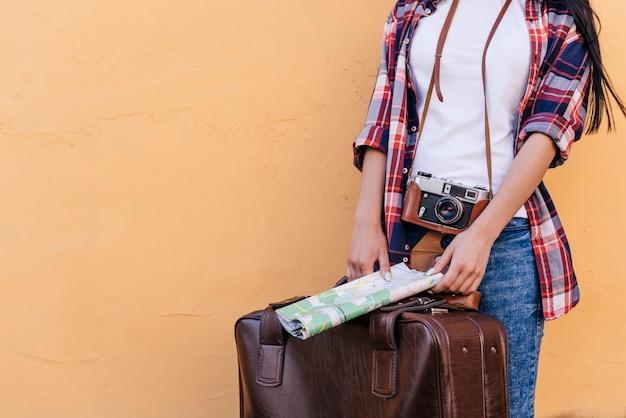 Sección media del viajero femenino que sostiene el mapa y la bolsa de equipaje con la cámara de pie cerca de la pared de melocotón Foto gratis
