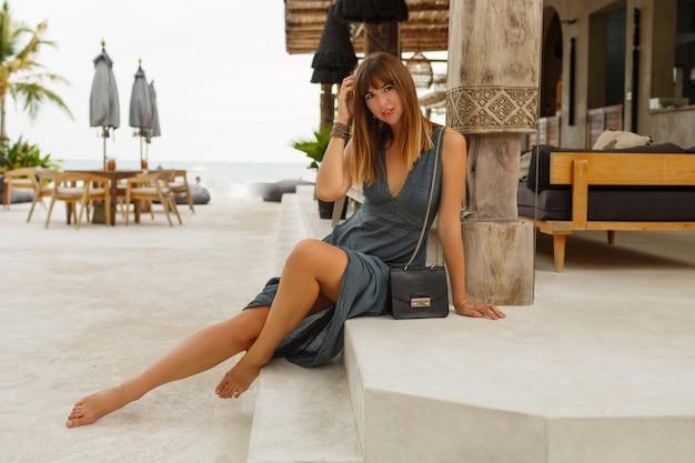 Seductora mujer morena en sexy vestido posando en un elegante restaurante de playa en estilo asiático. Foto gratis