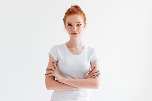Segura mujer de jengibre en camiseta posando con los brazos cruzados y mirando Foto gratis
