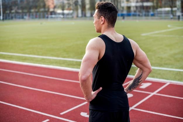 Seguro atleta masculino musculoso en pista roja mirando a otro lado Foto gratis