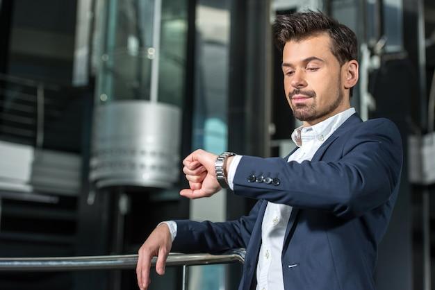 Seguro empresario está mirando el reloj. | Descargar Fotos