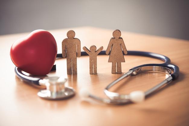 Seguro médico con familia y estetoscopio en escritorio de madera Foto Premium