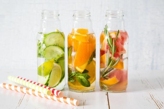 Selección de agua infundida en botellas de vidrio, fondo de madera rústica Foto Premium