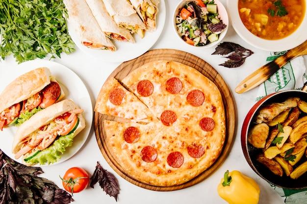 Selección de comida rápida que incluye pizza, sándwiches, shaurma, ensalada, papas a la parrilla y sopa. Foto gratis