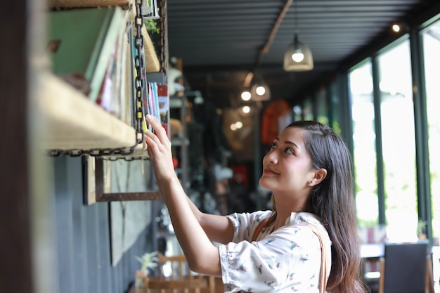 Selección de mujeres asiáticas libro para leer y sonreír y feliz relajarse en una cafetería Foto Premium