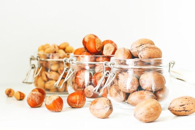 Selección de varias nueces: avellanas, pistachos y nueces en frascos de vidrio. Foto gratis