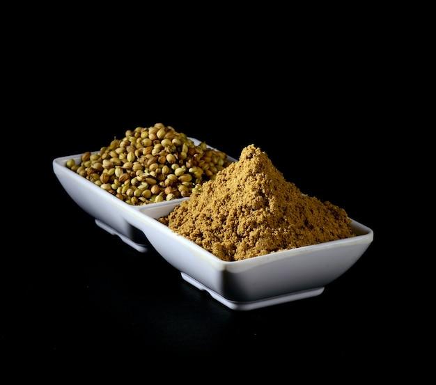Semillas de coriandro y polvo de coriandro en plato blanco sobre fondo negro. Foto Premium