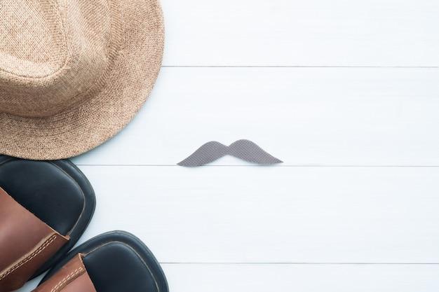 Señal de endecha plana creativa de bigote, sombrero de paja y zapatos en el fondo de madera blanca Foto Premium