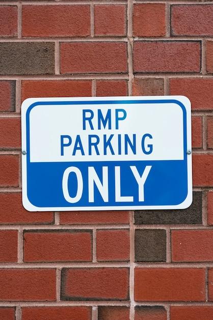 Señal de estacionamiento en primer plano de la pared de ladrillo Foto gratis