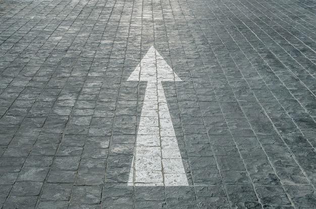 Señal de flecha pintada en blanco y viejo pálido en el piso de piedra de ladrillo negro en el aparcamiento Foto Premium