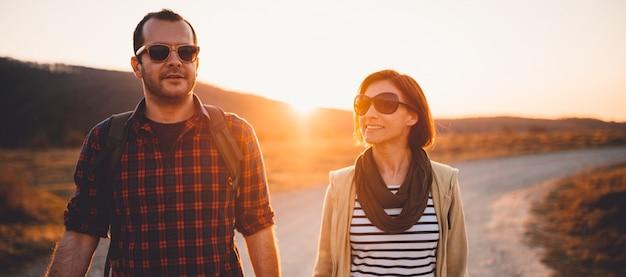 Senderismo feliz pareja en un camino de tierra durante el atardecer Foto Premium