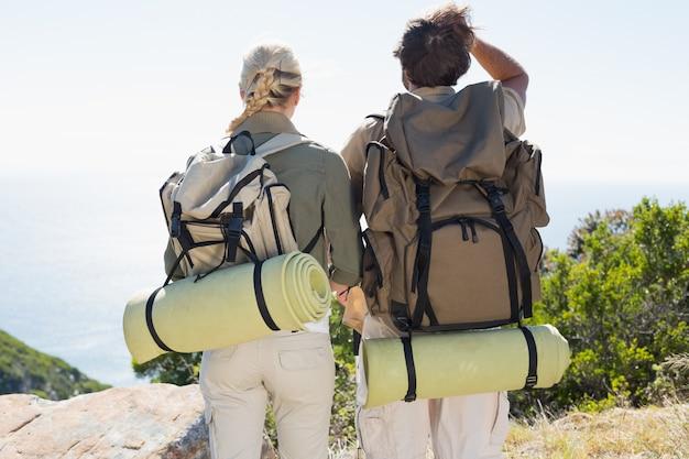 Senderismo pareja mirando la vista en la cumbre de la montaña Foto Premium