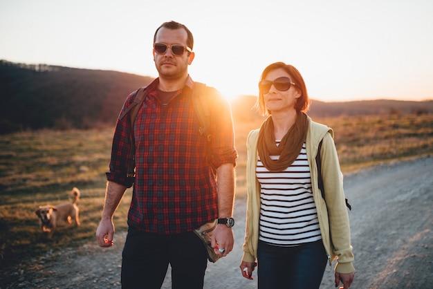 Senderismo pareja con perro en un camino de tierra durante el atardecer Foto Premium