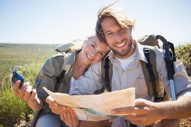 Senderismo pareja tomando un descanso en terreno de montaña con mapa y brújula Foto Premium