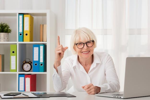 Senior con anteojos sentado en su oficina Foto gratis