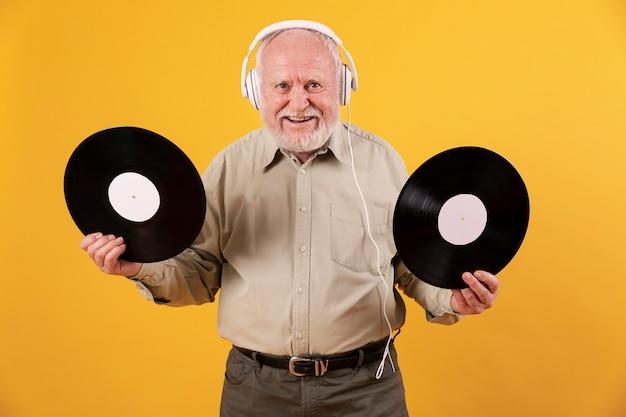 Senior en casa feliz con discos de música Foto gratis