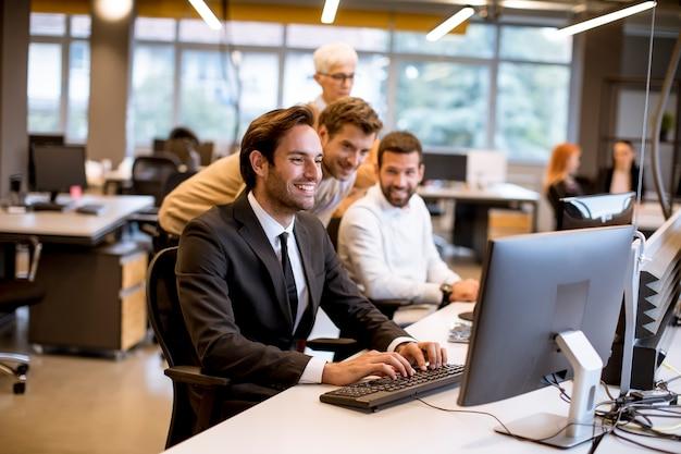 Senior empresaria y jóvenes empresarios trabajan en una oficina moderna Foto Premium