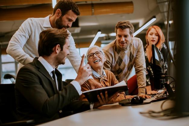 Senior empresaria trabajando junto con jóvenes empresarios en la oficina moderna Foto Premium