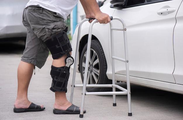 Senior hombre abre la puerta del coche con un andador en la carretera Foto Premium