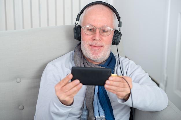 Senior hombre en auriculares escuchando música en casa Foto Premium