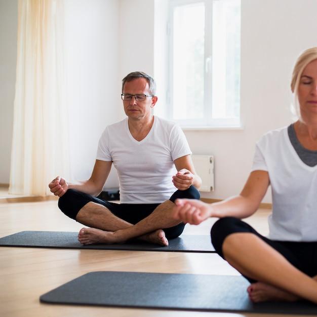 Senior hombre y mujer meditando sobre colchonetas de yoga Foto gratis