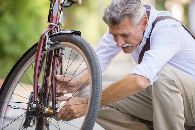 Senior hombre está reparando bicicleta en la calle. Foto Premium