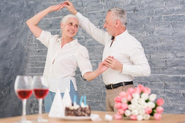 Senior marido y mujer bailando en la fiesta de cumpleaños Foto gratis