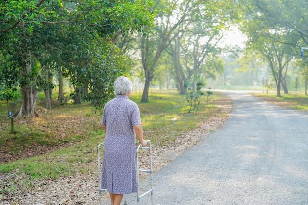 Senior mujer caminar con walker en el parque. Foto Premium