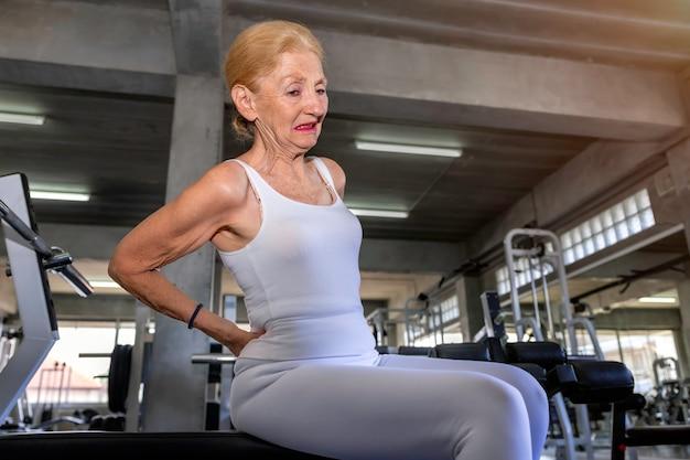 Senior mujer caucásica dolor de espalda durante el entrenamiento en el gimnasio. Foto Premium