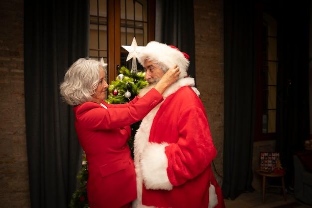 Senior mujer configurar hombre como santa claus Foto gratis