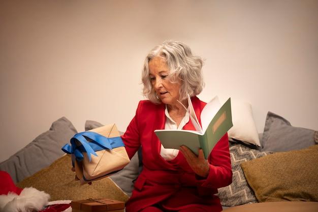 Senior mujer feliz con libro y regalo Foto gratis