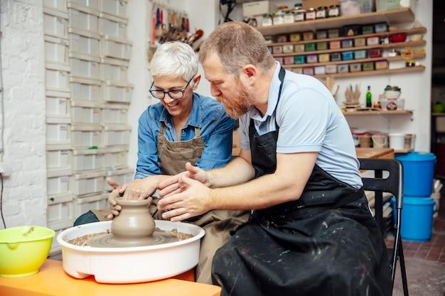 Senior mujer girando arcilla sobre una rueda con el maestro en la clase de cerámica Foto Premium
