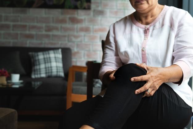 Senior mujer que sufre de dolor de rodilla en casa, problema de salud Foto Premium