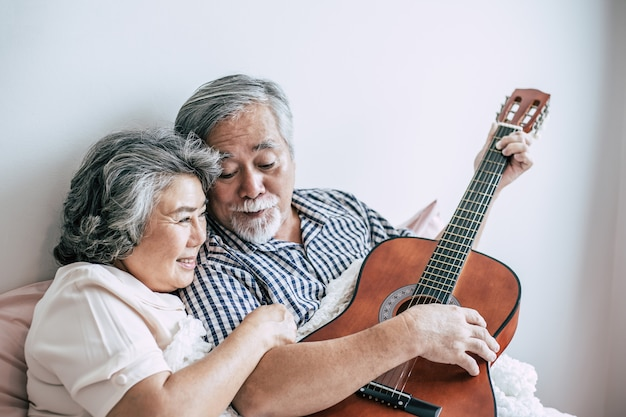 Senior par relajarse tocando guitarra acústica en la habitación de la cama Foto gratis