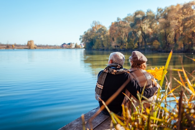 Senior pareja relajante en otoño lago. feliz hombre y mujer disfrutando de la naturaleza y abrazos sentado en el muelle Foto Premium