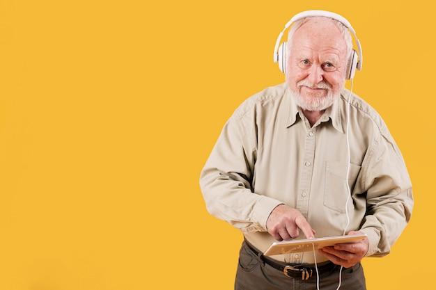 Senior tocando música en tableta Foto gratis