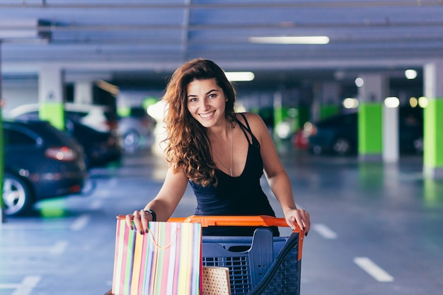 Señora alegre en elegante vestido negro llevando bolsas de colores en un estacionamiento cerca de un coche. Foto Premium
