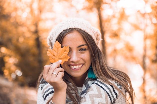 Señora alegre con hoja de otoño Foto gratis