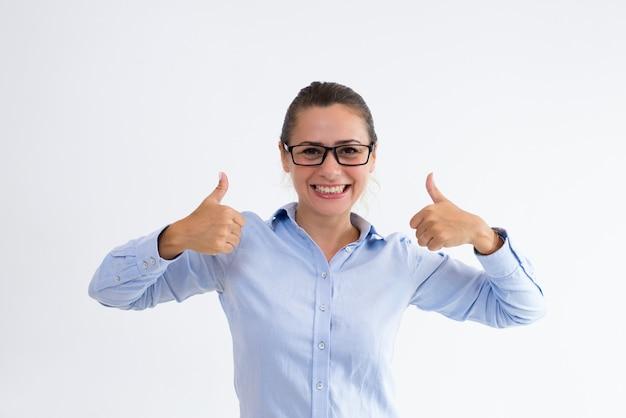 Señora alegre del negocio que muestra los pulgares para arriba y que mira la cámara Foto gratis