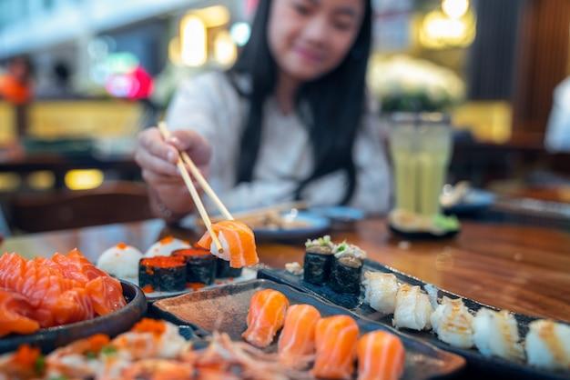 Señora asiática comer un sashimi de pescado de salmón y sushi en restaurante japonés Foto Premium