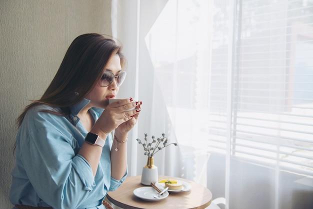 Señora asiática joven feliz del retrato en cafetería Foto gratis