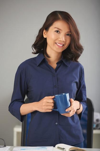 Señora asiática posando con taza Foto gratis