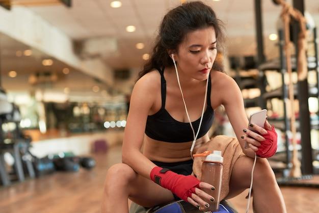 Señora atlética asiática tomando descanso de entrenamiento en el gimnasio Foto gratis
